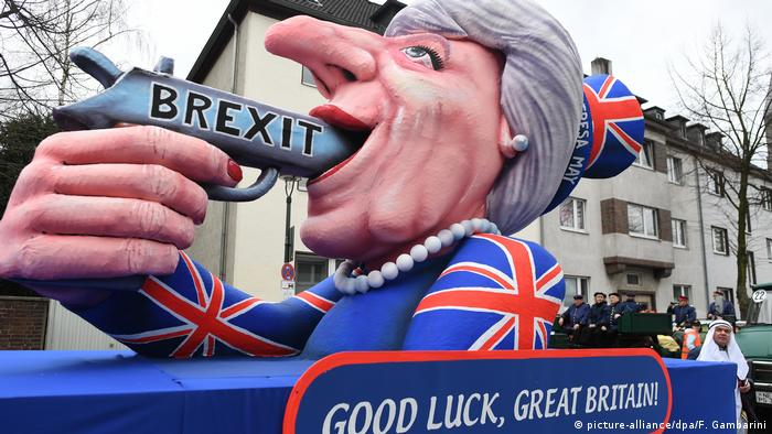 Тереза Мэй стреляет в себе в рот из пистолета с надписью Brexit.
