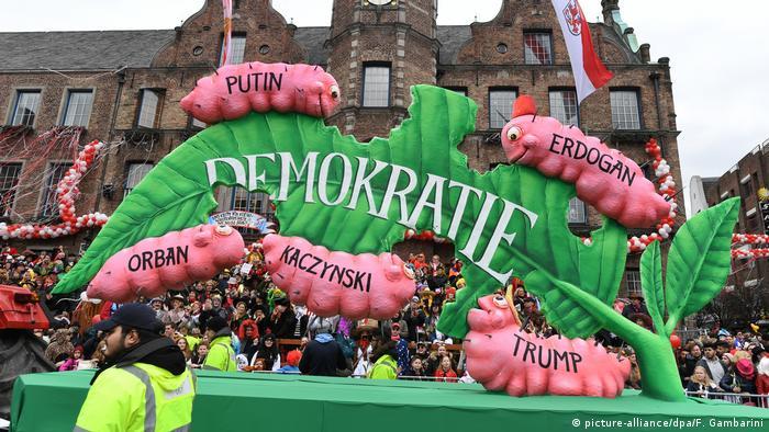 Зеленый лист с надписью демократия едят гусеницы: Путин, Эрдоган, Орбан, Качиньский и Трамп.