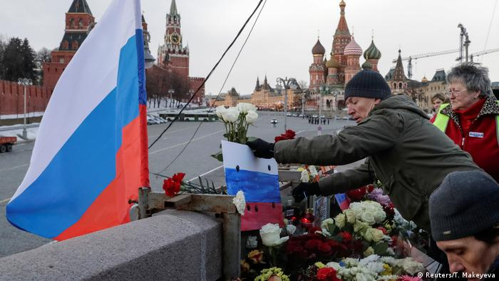 People place flowers at the site of the assassination of Kremlin critic Boris Nemtsov after a rally to mark the anniversary of his murder