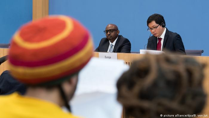 UN experts Sabelo Gumedze and Ricardo Sunga presenting their findings on racism in Germany. In the foreground, a man of African descent listens.