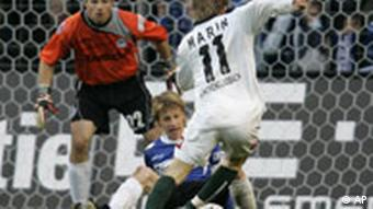 Bielefeld players challenge Moenchengladbach's Marko Marin for the ball