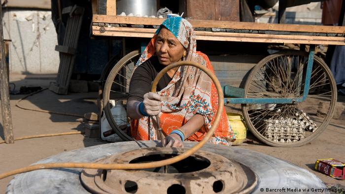 """Shanti Devi trabaja en el área de servicio más grande de Nueva Delhi. Su marido y ella tienen un taller desde hace 20 años. Todos los días hace cambios de neumáticos y repara los camiones. """"Es un trabajo sucio, nada para personas sensibles"""", señala. Su marido está muy orgulloso. Para muchos clientes, tener una mujer como mecánico es raro todavía."""