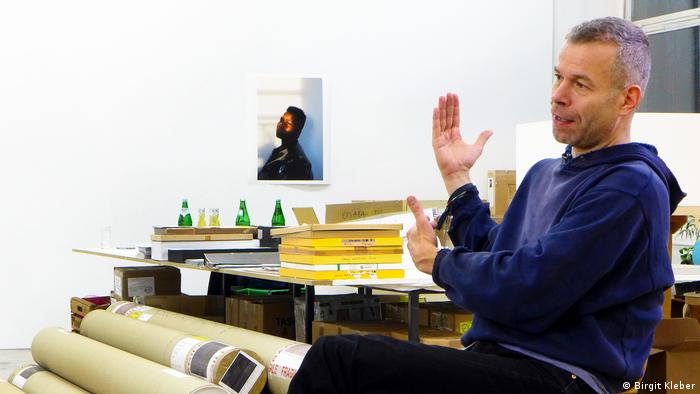 A man sits holding his hands up