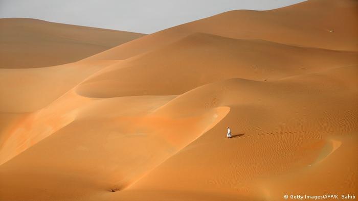 A man stands in an endless sandy desert