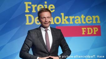 Christian Lindner of the FDP stands in front of a party sign (picture-alliance/dpa/T. Hase)