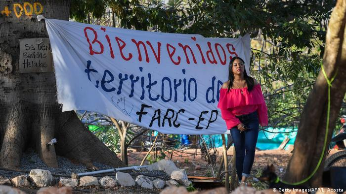 A woman stands in front of a sign reading welcome to FARC territory