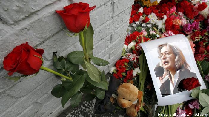 Фотография Анны Политковской и цветы на входе в здение, где она была убита