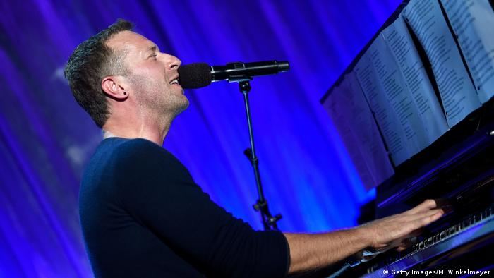 Coldplay frontman Chris Martin plays the piano and sings into a microphone (Getty Images/M. Winkelmeyer)