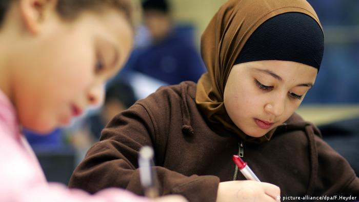 Muslim girl writing at school