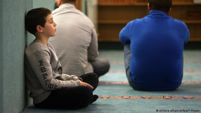 A boy sits in prayer at the Cathedral Mosque of the Tatar village Belozyorye
