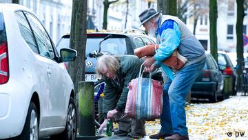 Two homeless men collecting empty bottles on the street