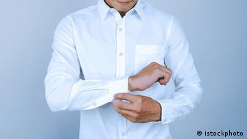 Ein Mann knöpft sich den Ärmel seines weißen Hemdes zu