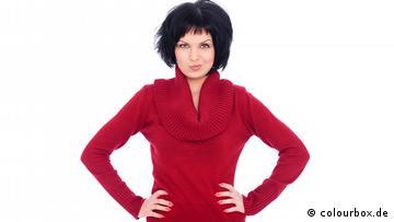 Eine dunkelhaarige Frau, die einen roten Rollkragenpullover trägt