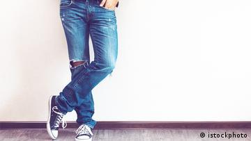 Beine, die in zerrissenen blauen Jeans stecken