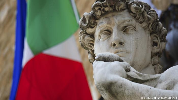 Michelangelo's statue of David in front of an Italian flag
