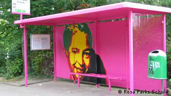 A pink bus stop with a mural (c) Rosa Parks Schule