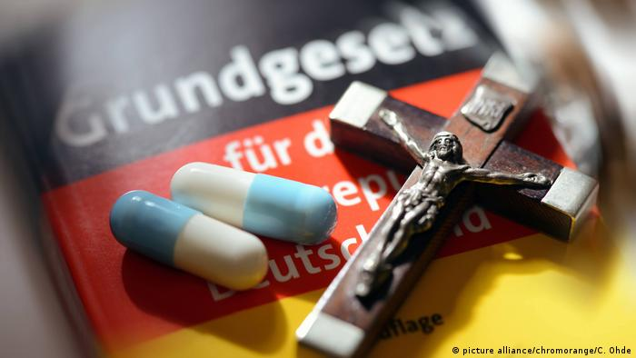 The German constitution and a cross, next to pills for self-determined dying, a still life