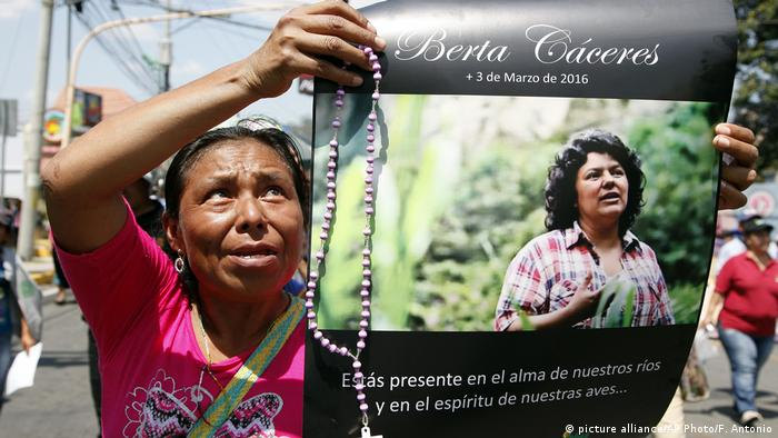 A woman holds up a poster with a photo of slain environmental leader Berta Caceres during a protest in Tegucigalpa, Honduras