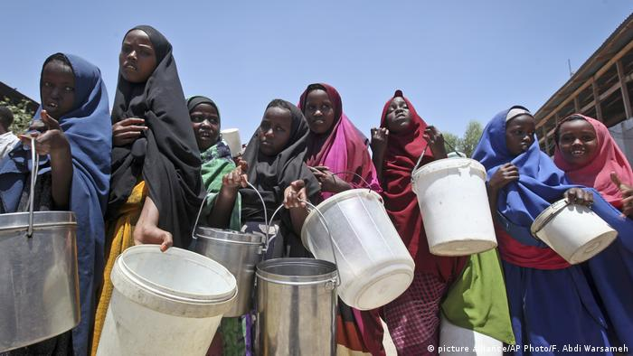 A group of Somali women line up with buckets to get food hand-outs. (picture alliance/AP Photo/F. Abdi Warsameh)