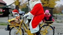 Ein Weihnachtsmann faehrt am Montag, 10. November 2008, mit zwei Kindern auf seinem Fahrrad durch das nordbrandenburgische Dorf Himmelpfort. Er eroeffnete dort eines der bekanntesten deutschen Weihnachtspostaemter. Im vergangenen Jahr schrieben 280.000 Kinder ihre Wunschzettel an die Adresse Weihnachtsmann, Weihnachtspostfiliale, 16798 Himmelpfort. (AP Photo/Sven Kaestner) ---A Santa Claus on his bike carries two kids through the village of Himmelpfort (Heaven's Gate) about 100 kilometres north of Berlin, Germany. There he opened a German Christmas mail office. Last year about 280.000 children wrote their wishes to the address Santa Claus, Christmas post office, 16798 Himmelpfort, Germany. (AP Photo/Sven Kaestner)