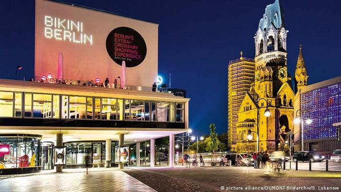 An illuminated nighttime shot of Berlin's Kaiser-Wilhelm Memorial Church, across the street from a giant billboard that reads: Bikini Berlin.