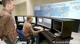 Two German software engineers work on a monitoring computers of the Tsunami Warning System centre in Jakarta