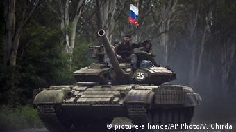 Пророссийские сепаратисты в Донбассе на современном танке с российским флагом.