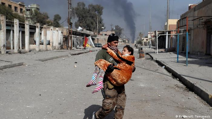 An Iraqi special forces soldier carries a woman injured during a battle between Iraqi forces and IS fighters in Mosul.