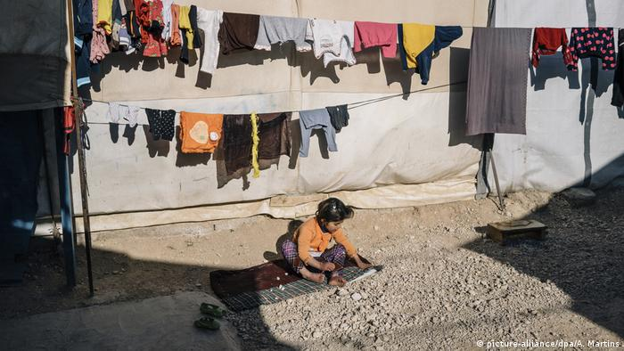 Child sitting on stony ground, laundry fluttering on lines overhead (picture-alliance/dpa/A. Martins)