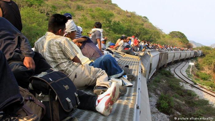 Central american migrants travel on the roof of a train near to the Medias Aguas stretch in Mexico