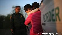 one-year-old from El Salvador clings to his mother after she turned themselves in to Border Patrol agents