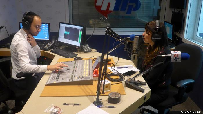 Journalistin Rachel Fastag-Klein sits in front of a microphone presenting her radio show in a studio