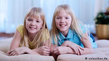 Zwei gleichaussehende Mädchen liegen nebeneinander