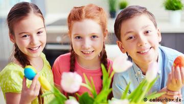 Ein Junge sitzt neben zwei Mädchen, sie halten Ostereier hoch