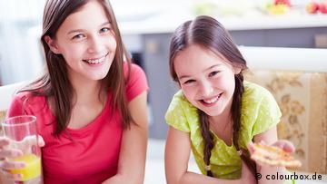 Zwei Mädchen sitzen nebeneinander, eine hält ein Glas O-Saft, die andere ein Stück Pizza in der Hand