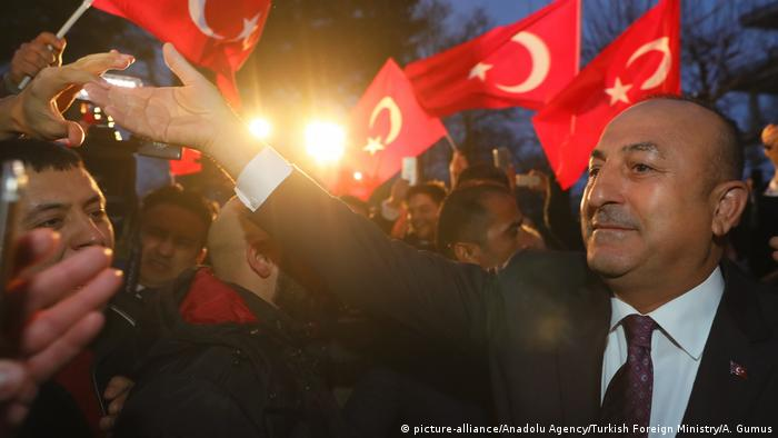Mevlut Cavusoglu surrounded by a crowd in Hamburg waving Turkish flags