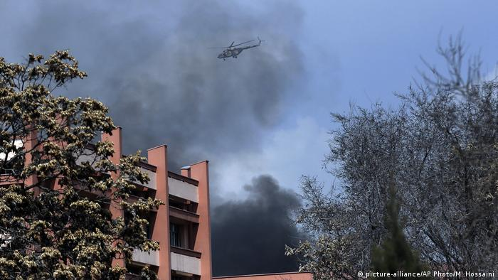 Against a backdrop of black smoke, a helicopter flies over a military hospital in Kabul (picture-alliance/AP Photo/M. Hossaini)