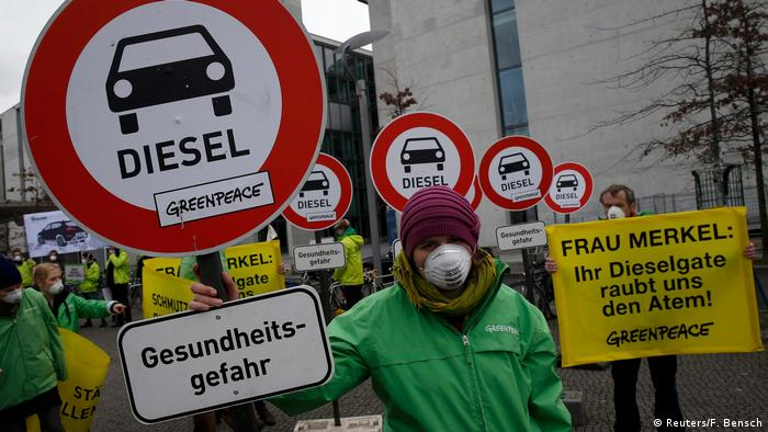 Environmental protesters holding signs against the use of diesel cars in Germany