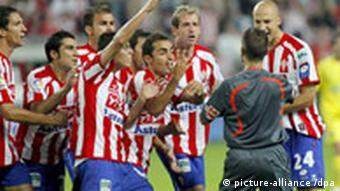 Fußballspieler bedrängen den Schiedsrichter