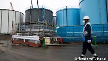 1.3.2017*** A Tokyo Electric Power Co.'s (TEPCO) employee walks past storage tanks for contaminated water at the company's Fukushima Daiichi nuclear power plant in Okuma, Fukushima, Japan, February 23, 2017. REUTERS/Tomohiro Ohsumi/Pool