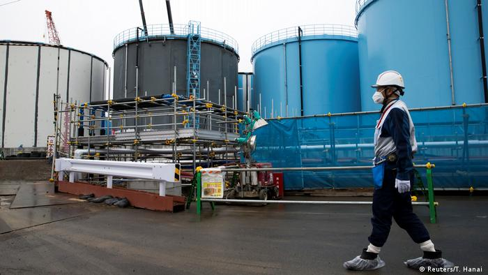 An employee walks past storage tanks for contaminated water at the Fukushima nuclear power plant in Okuma, Japan