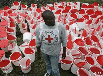 A Red Cross worker waits to distribute buckets to displaced people in DR Congo