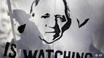 A banner reading is watching you underneath an image of former interior minister wolfgang schäuble