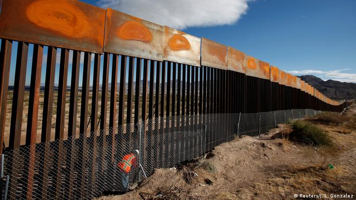 A U.S. worker inspects a section of the U.S.-Mexico border wall