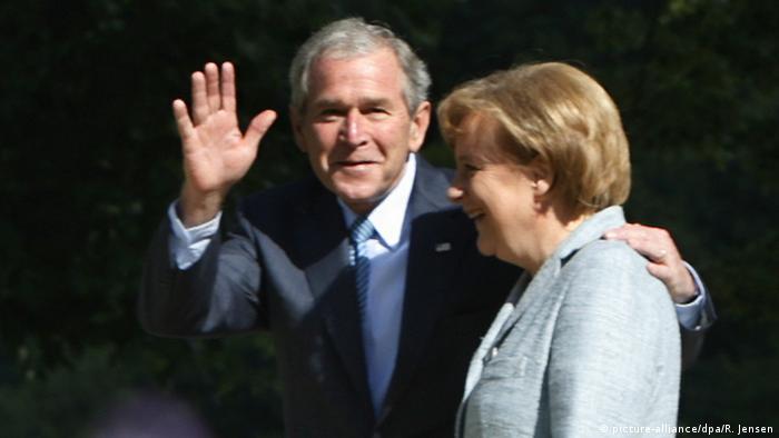 Bush waving at camera with hand on Merke's shoulder in Meseberg