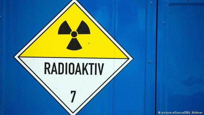 Symbolbild Radioaktivität - Radioaktivitätszeichen auf blauer Wand