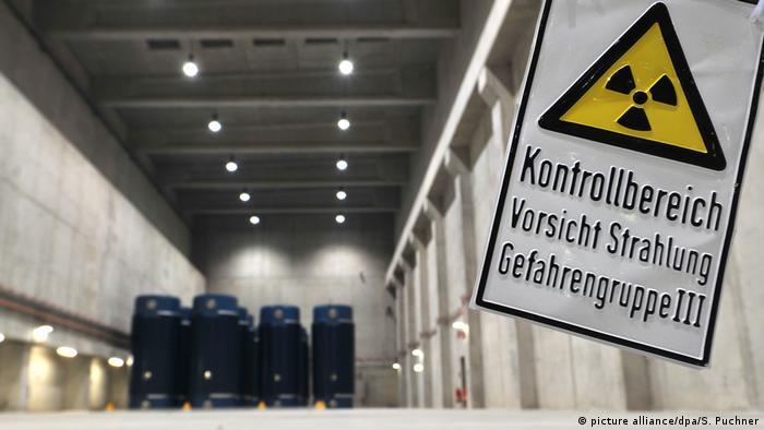 Symbolbild Radioaktivität - Atommüll - Castorbehälter im Hintergrund, im Vordergrund ein Schild Vorsicht Strahlung