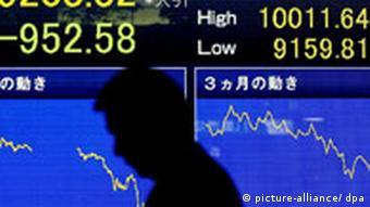 A Japanese businessman walks in front of a stock price indicator board in downtown Tokyo