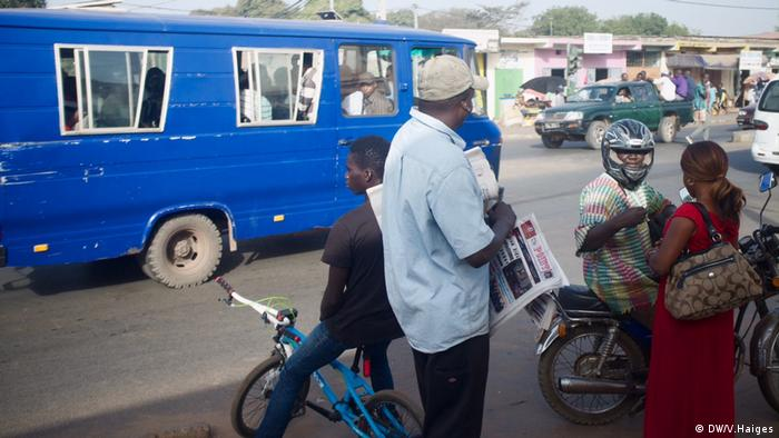Street scene with dark blue bus and newspaper vendor