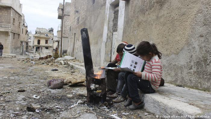 Children review manuals distributed by UNICEF-supported volunteers on the risks of unexploded remnants of war